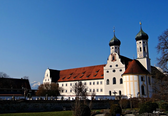 A small clock tower in front of a house with St. Nicholas\' Church, Tallinn in the background