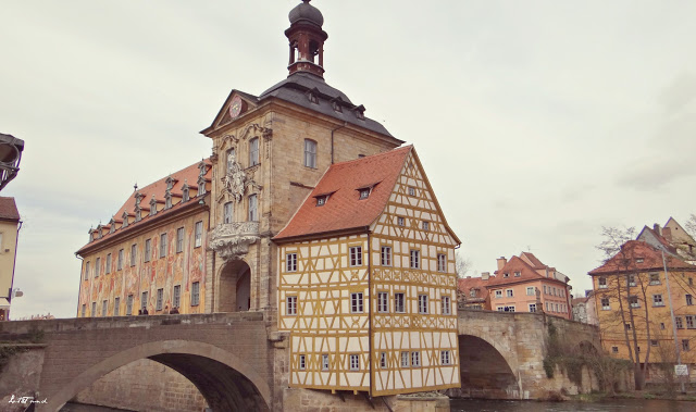 A large brick building with a clock tower with Bamberg in the background