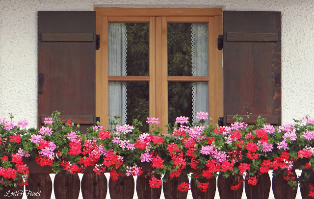 A vase filled with pink flowers in front of a building
