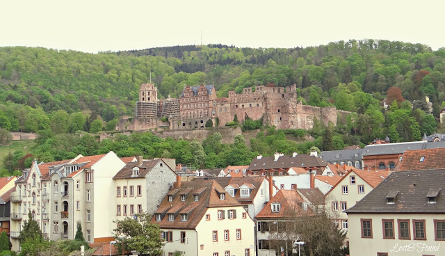 A small town with Heidelberg Castle in the background
