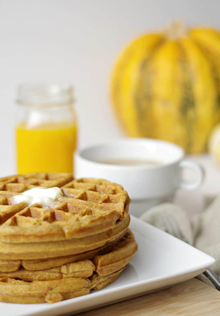 close up of 3 Pumpkin Gingerbread Waffles on white plate with coffee and orange juice near by