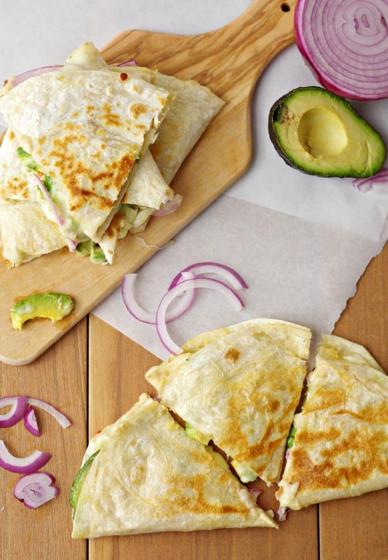 Hummus, Avocado and Cheese Quesadillas on wood plank