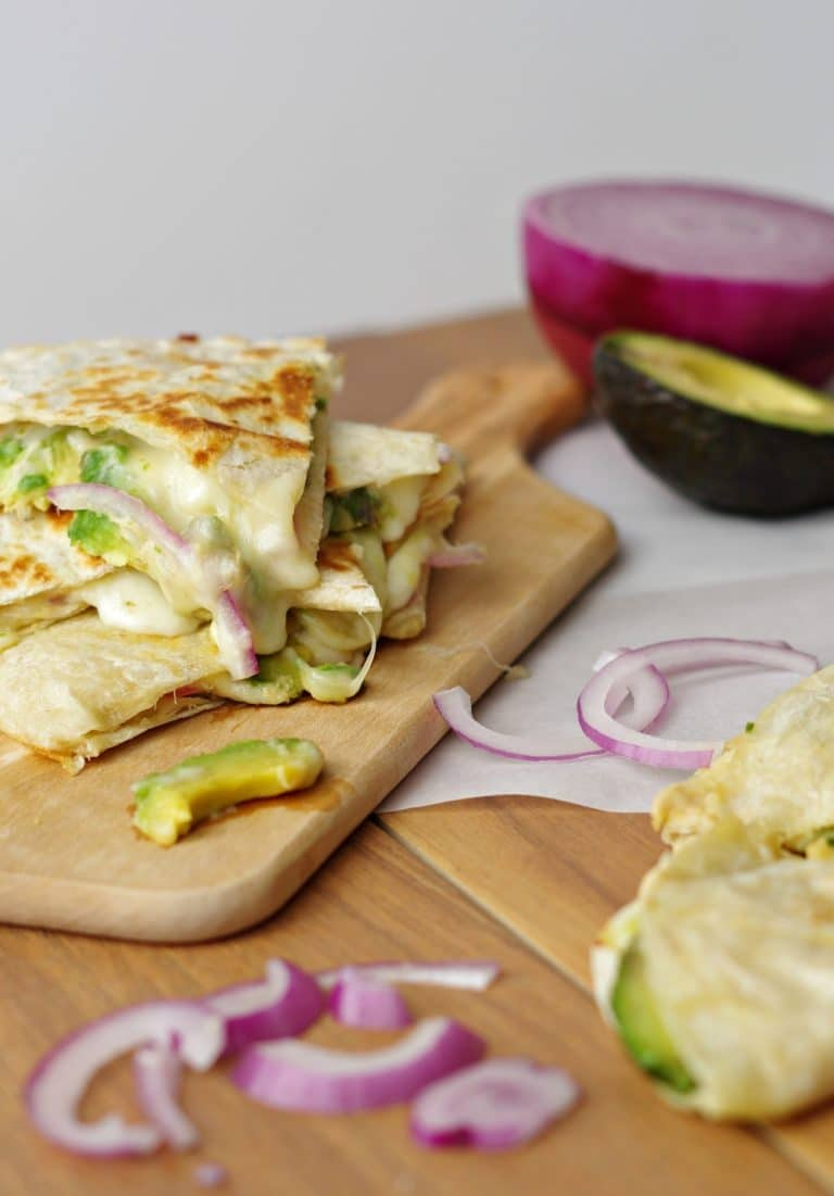 close up of dripping cheese Hummus, Avocado and Cheese Quesadillas on wood plank