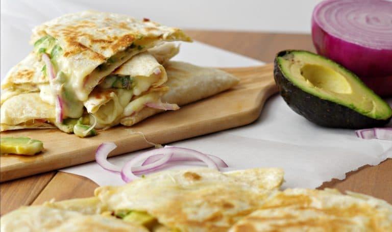 Hummus, Avocado and Cheese Quesadillas on wood plank close up horizontal