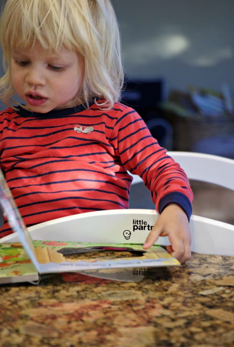 child on Learning Tower reading book
