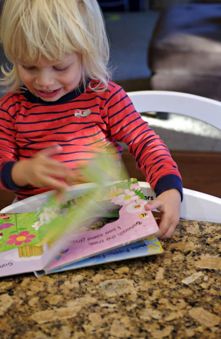 child on Learning Tower flipping pages in book