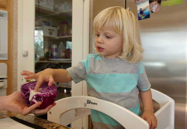 child on Learning Tower looking into Kitchen touching purple cabbage