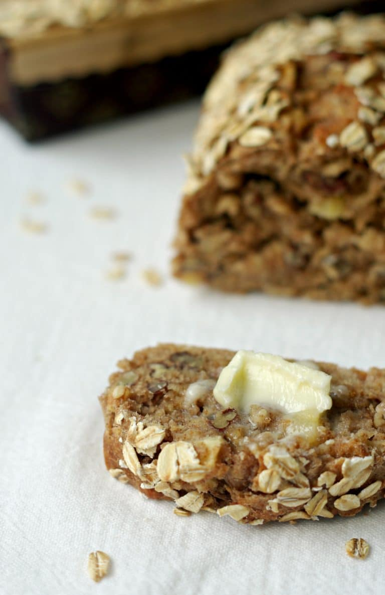 sliced Apple Cinnamon Oatmeal Bread with large chunk of butter