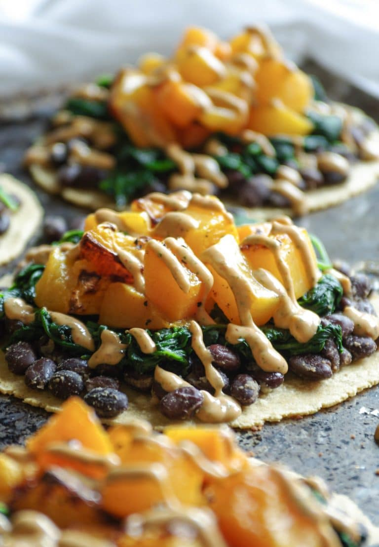 close up of tortillas with black beans, cooked spinach, roasted butternut squash, and chipotle lime crema