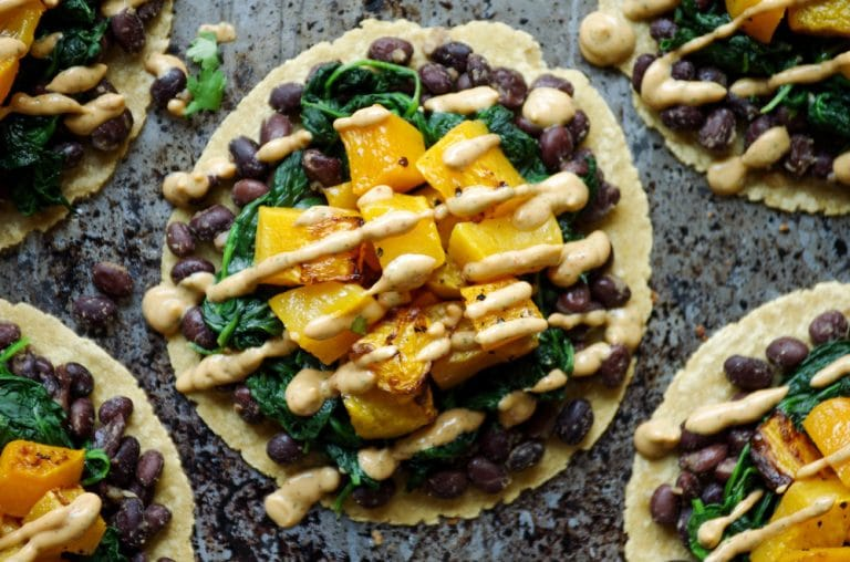 overhead image of tortillas with black beans, cooked spinach, roasted butternut squash, and chipotle lime crema