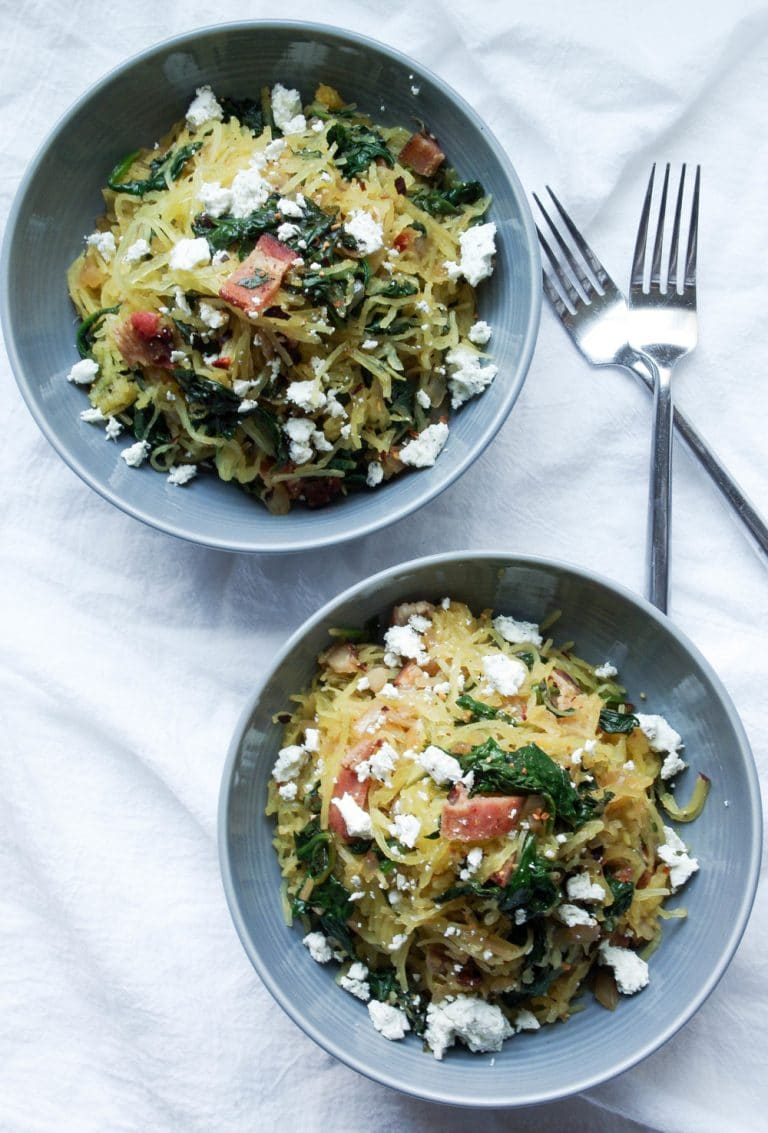 two Grey bowls full of Spaghetti Squash with Bacon, Spinach, and Goat Cheese