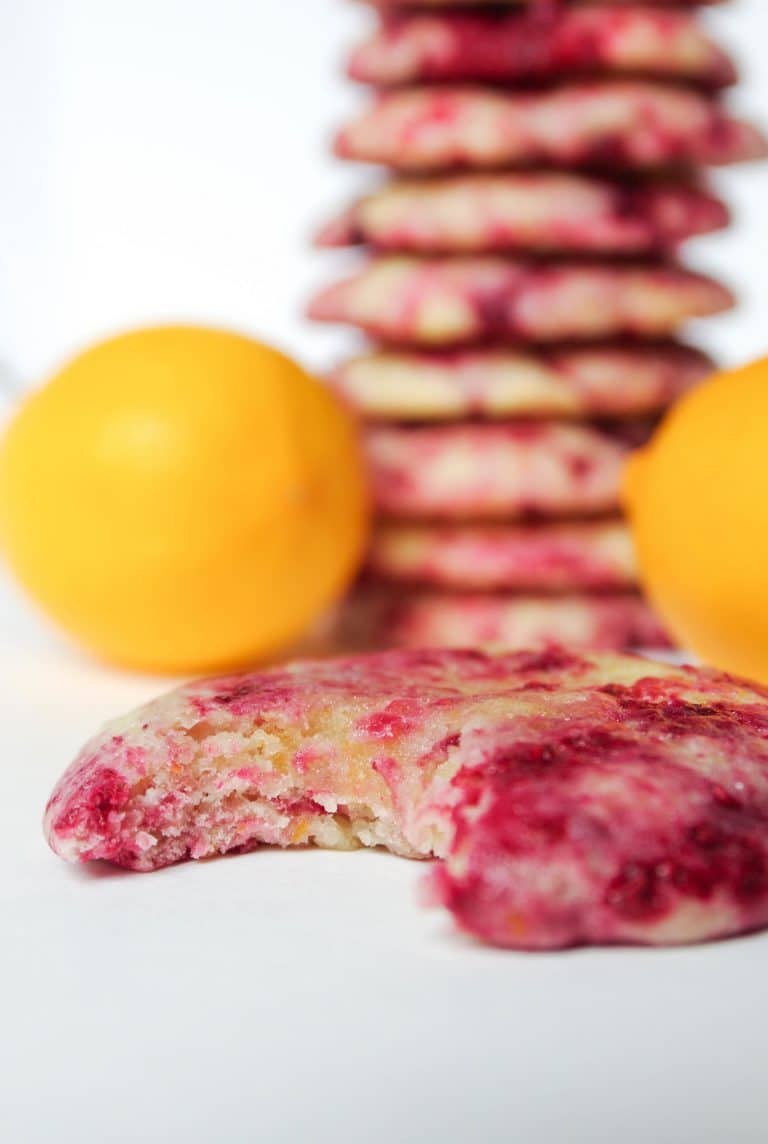 Single bite taken out of cookie made with lemon and raspberries