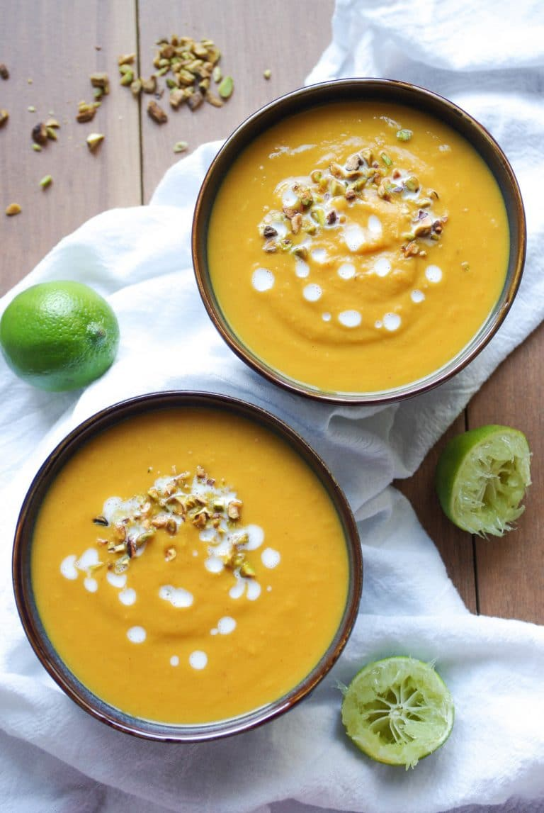 two bowls of Thai Pumpkin and Sweet Potato Soup with squeezed limes