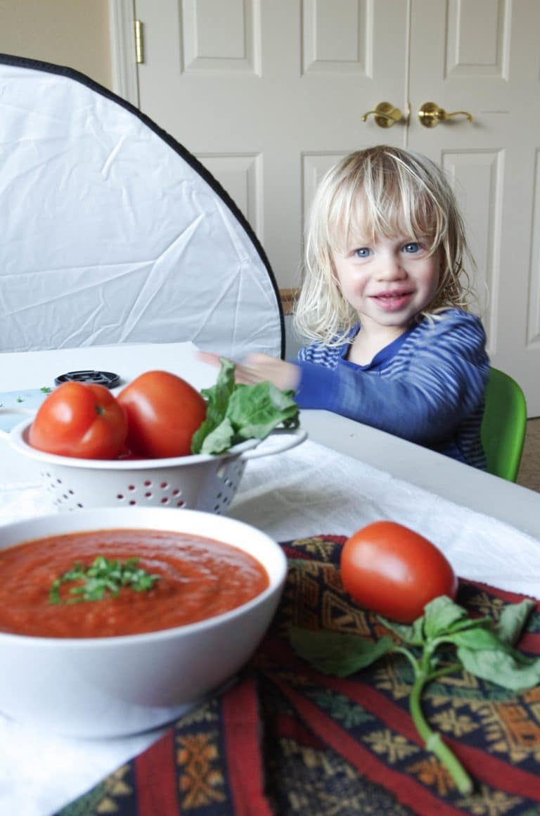 Three year old boy helping with tomato basil soup photoshoot.