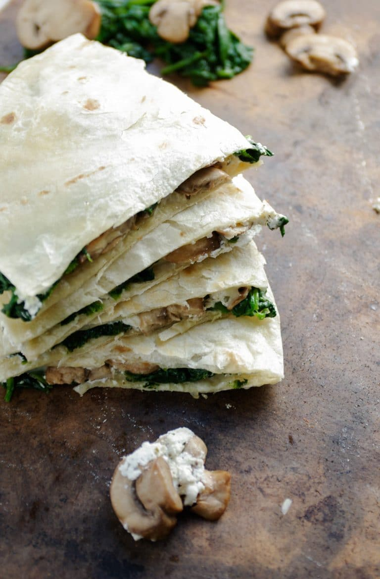 Quartered and Goat Cheese Quesadilla with scattered Mushrooms and Spinach in foreground