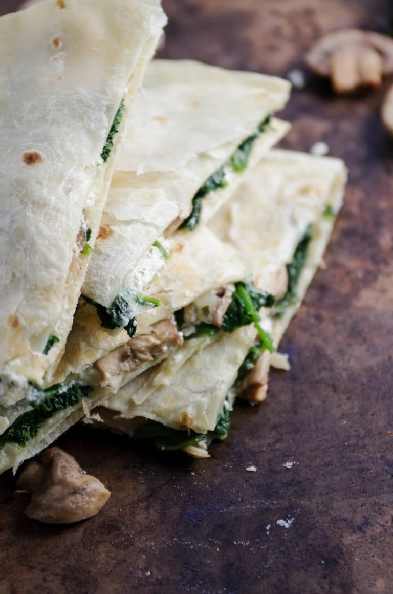 Quartered and stacked Goat Cheese Quesadilla with scattered Mushrooms and Spinach