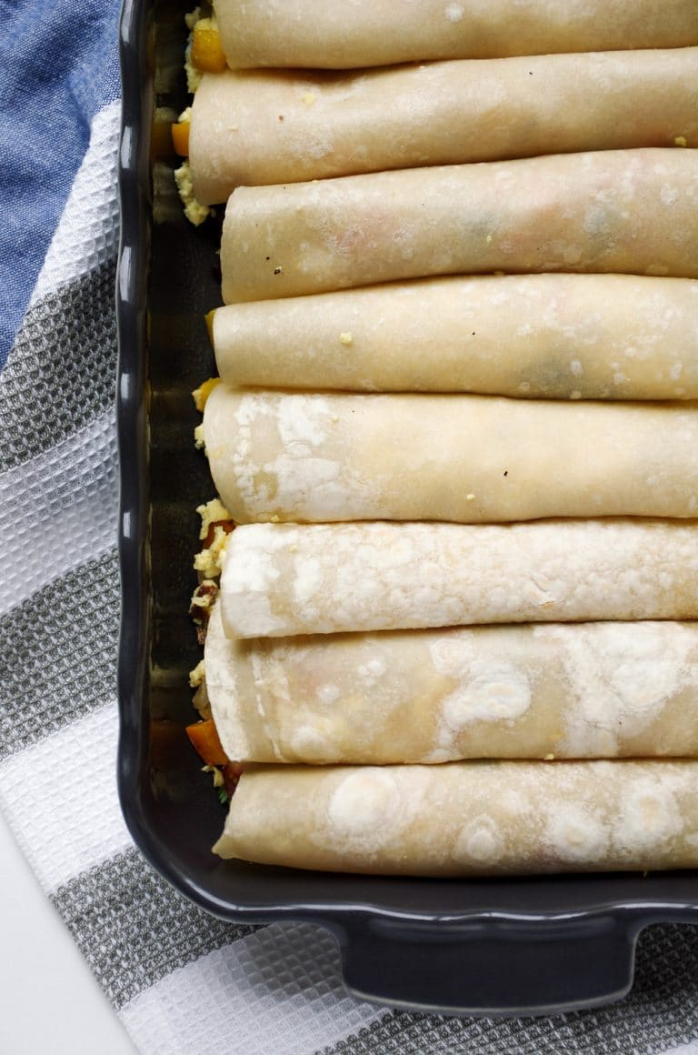 casserole dish of Breakfast Enchiladas filled with Bacon and Egg