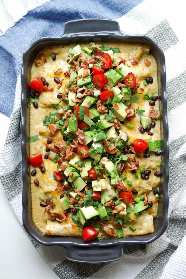 baked casserole dish of Breakfast Enchiladas filled with Bacon and Egg and Cheese Sauce