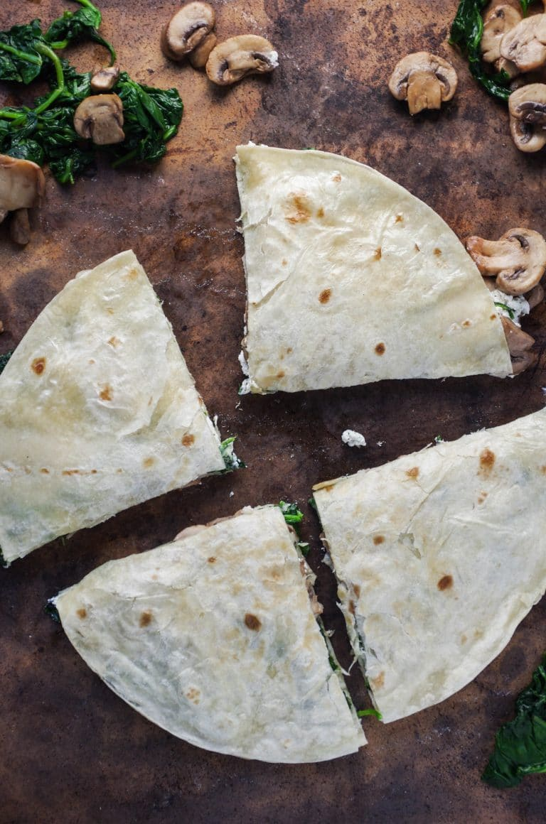 Quartered Goat Cheese Quesadilla with scattered Mushrooms and Spinach