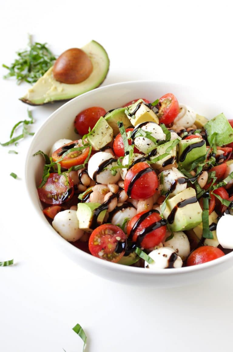 close up image of Caprese Salad with Avocado and Balsamic Glaze in white bowl