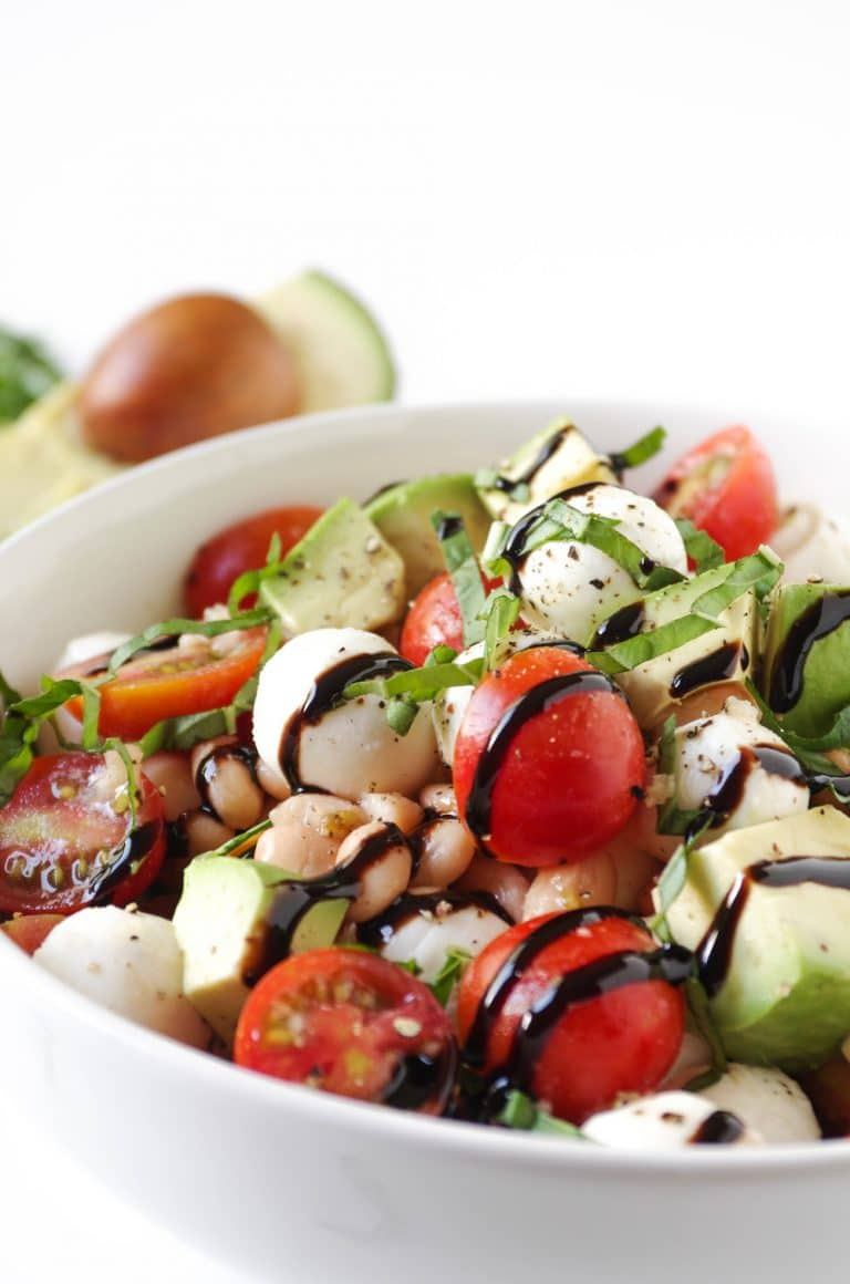 very close image of Caprese Salad with Avocado and Balsamic Glaze in white bowl
