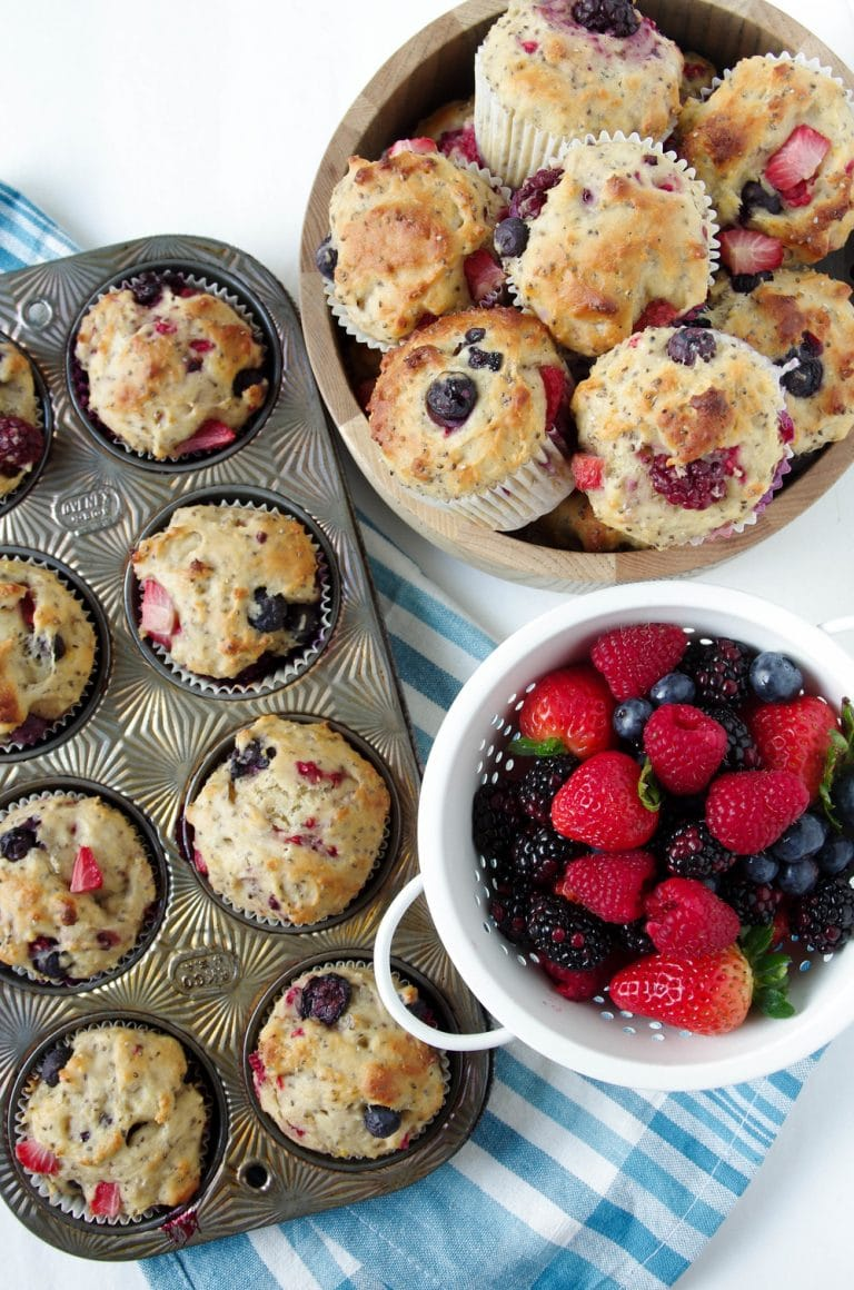 Super Berry Chia Muffins in pan and bowl with fresh berries in side bowl