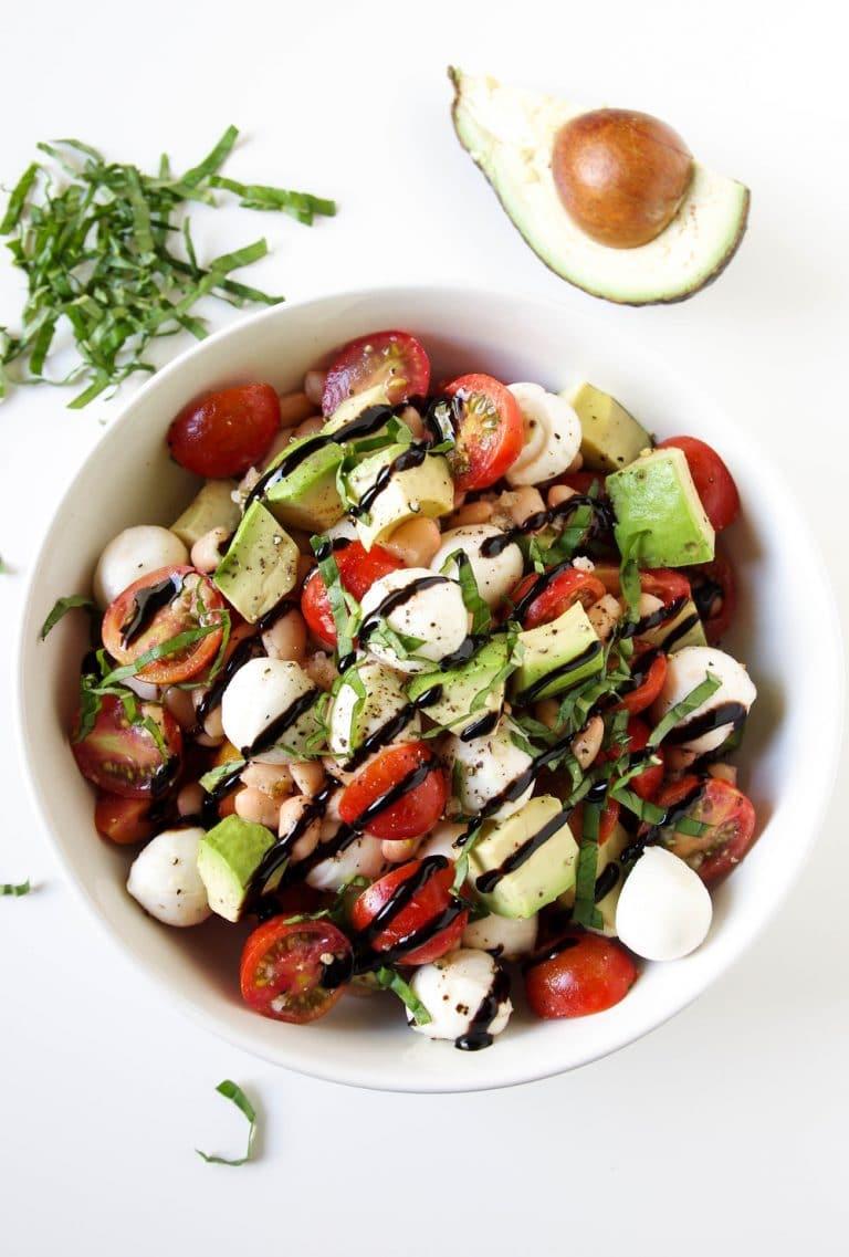 white bowl of Caprese Salad with Avocado and Balsamic Glaze
