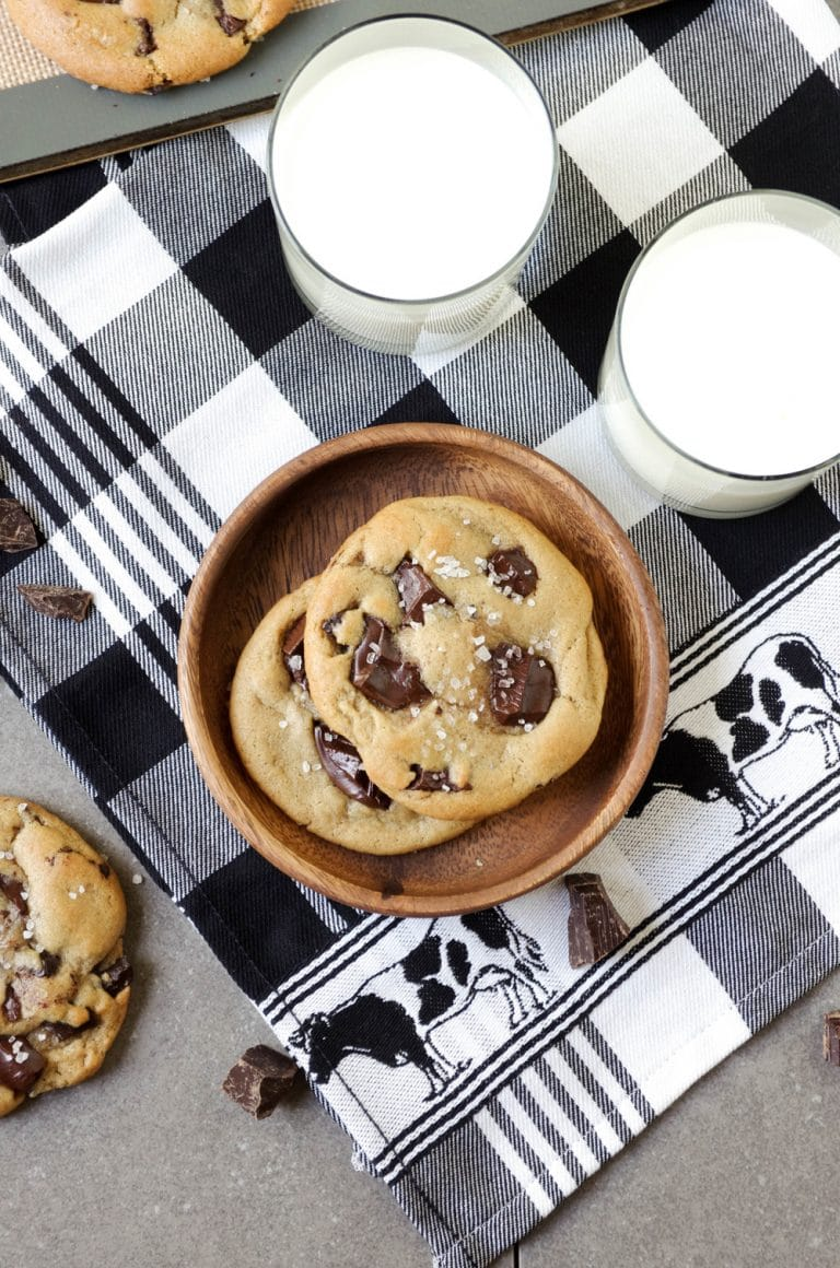 pile of Chocolate Chunk Cookies with 2 glasses of milk