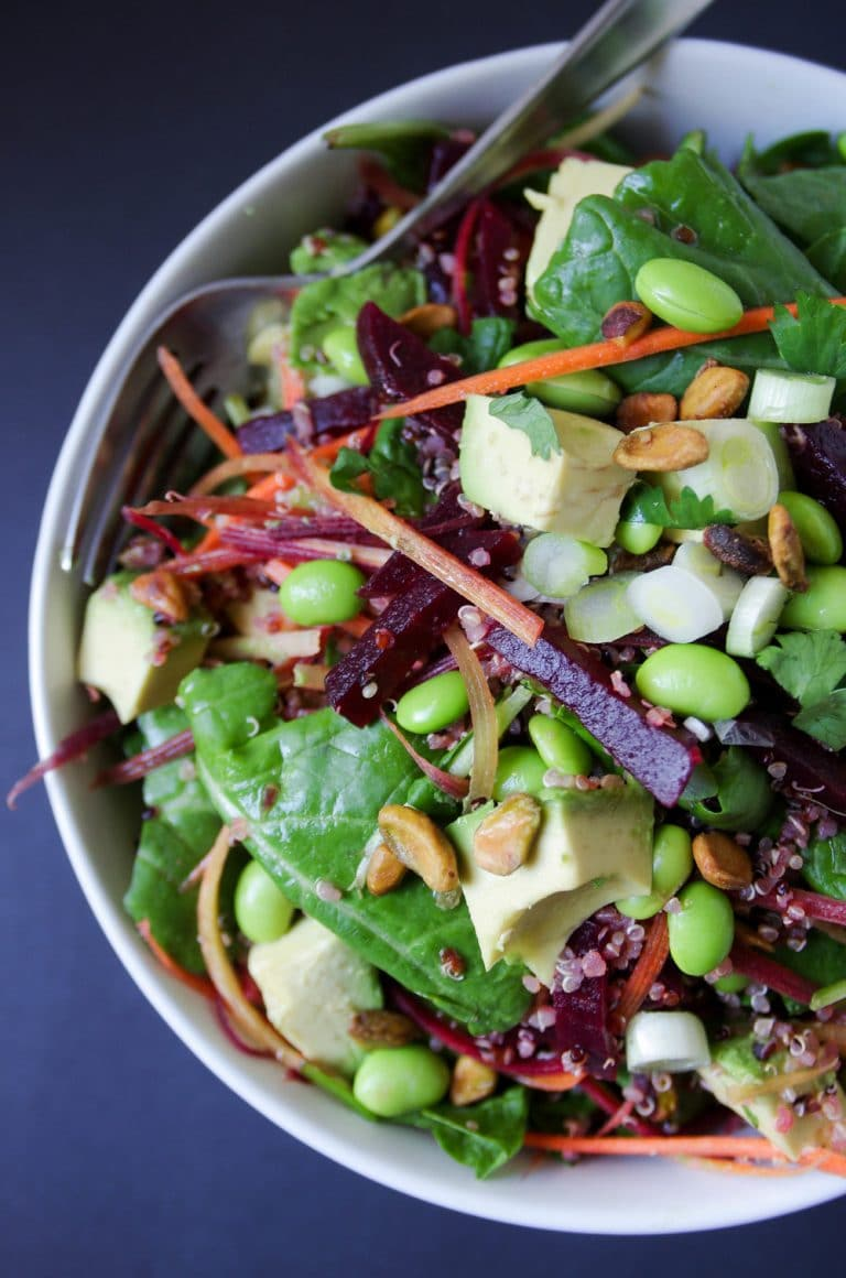 close up of Beet Avocado Quinoa Salad in white bowl with Herb Vinaigrette