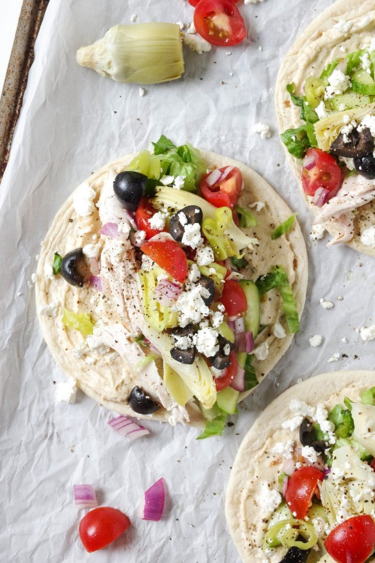 multiple Easy Mediterranean Chicken Wraps with Hummus on parchment paper
