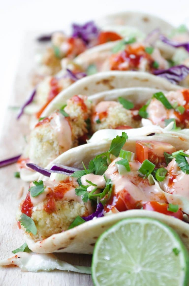4 Baked Bang Bang Cauliflower Tacos lined up on cutting board with lime