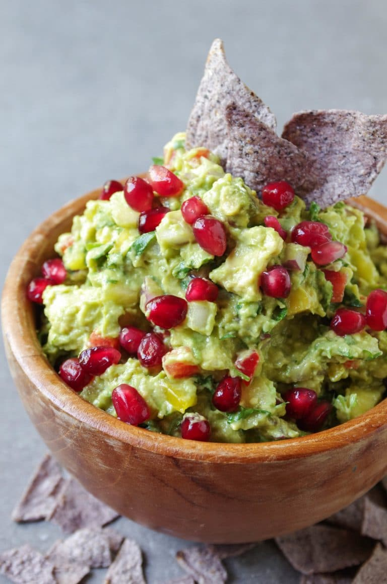 Mango Guacamole covered in pomegranates in wooden bowl with blue corn chips