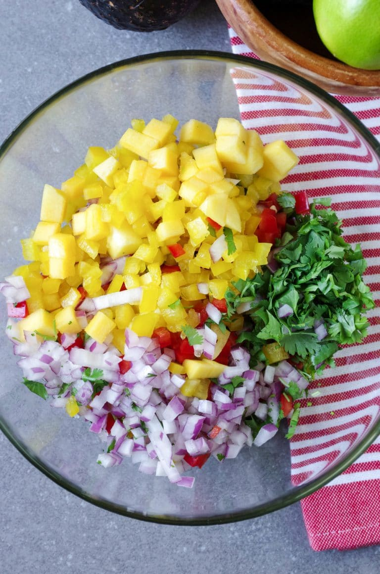 mango red onion cilantro and bell peppers in glass bowl