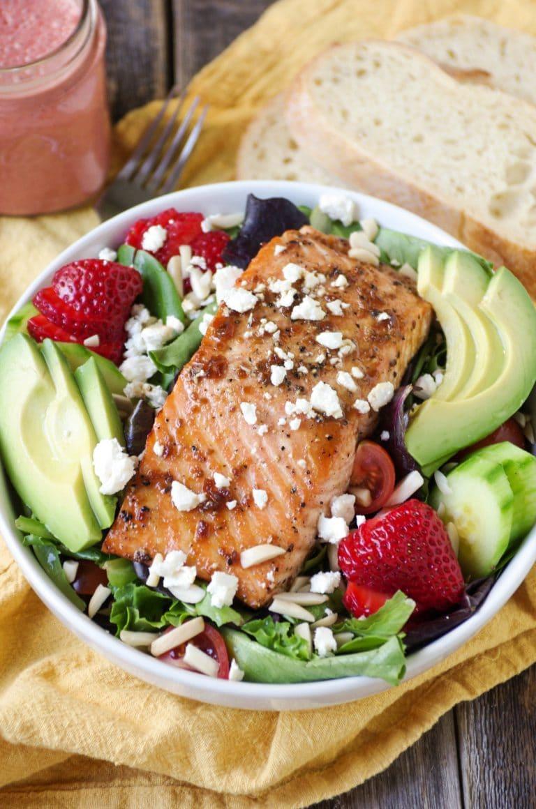 close up of Teriyaki Salmon Salad in white bowl with Strawberry Vinaigrette in mason jar