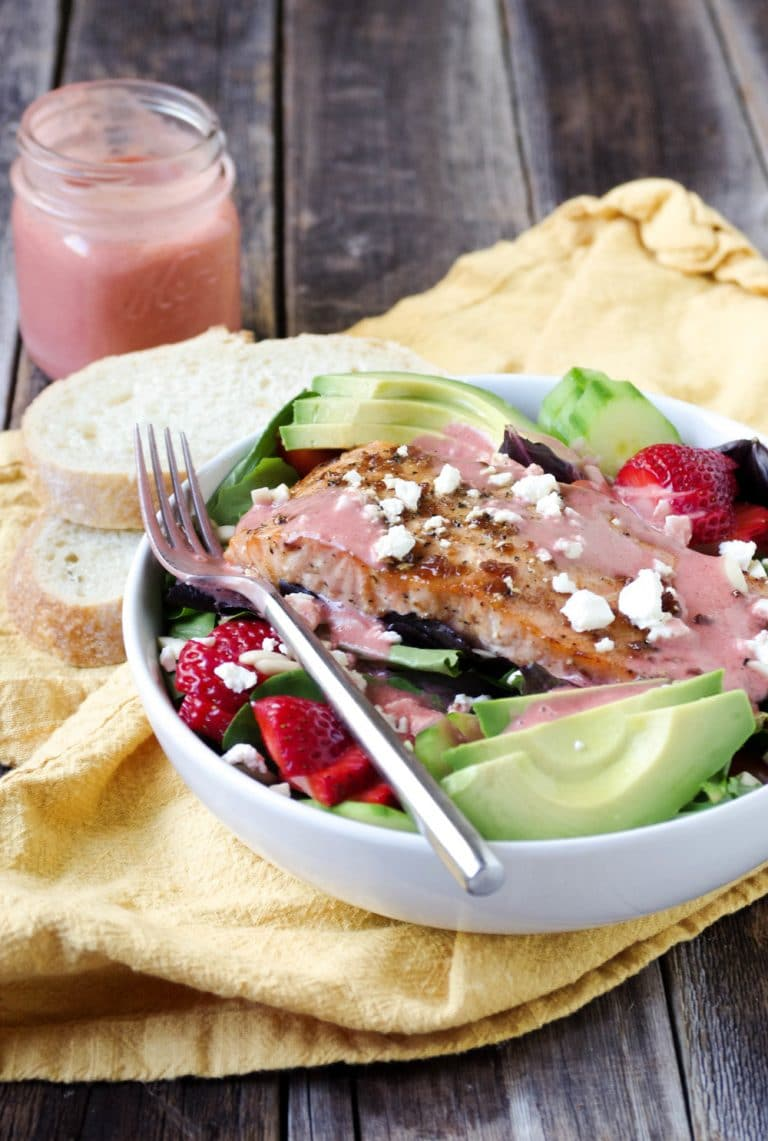 Teriyaki Salmon Salad drizzled with dressing in white bowl with Strawberry Vinaigrette in mason jar