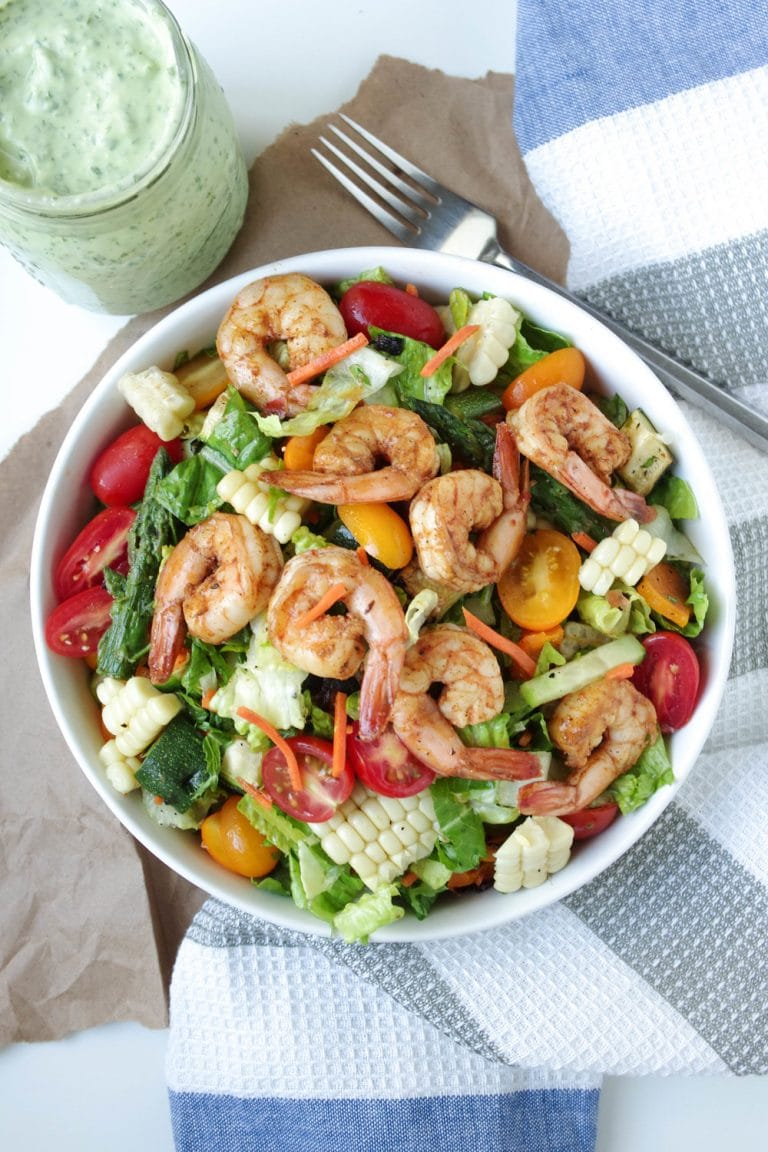 overhead image of Shrimp and veggie salad in white bowl with Avocado Cilantro Dressing