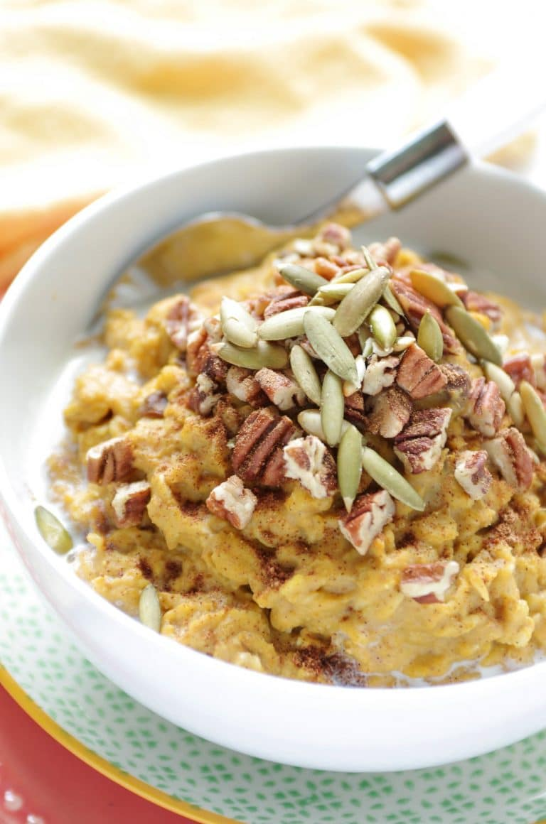 white bowl full of Easy Pumpkin Oatmeal covered in pecans and seeds
