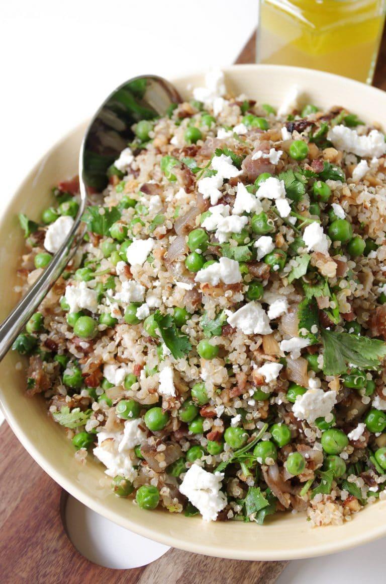 bowl full of Pea Quinoa Salad with Lemon Honey Vinaigrette in a jar behind
