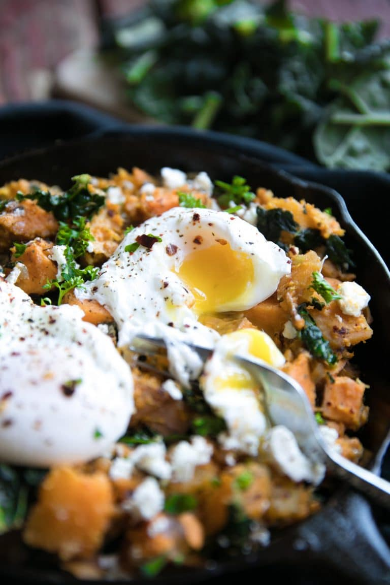 close up of skillet with Sweet Potato + Butternut Squash Hash with Feta and popped Poached Egg