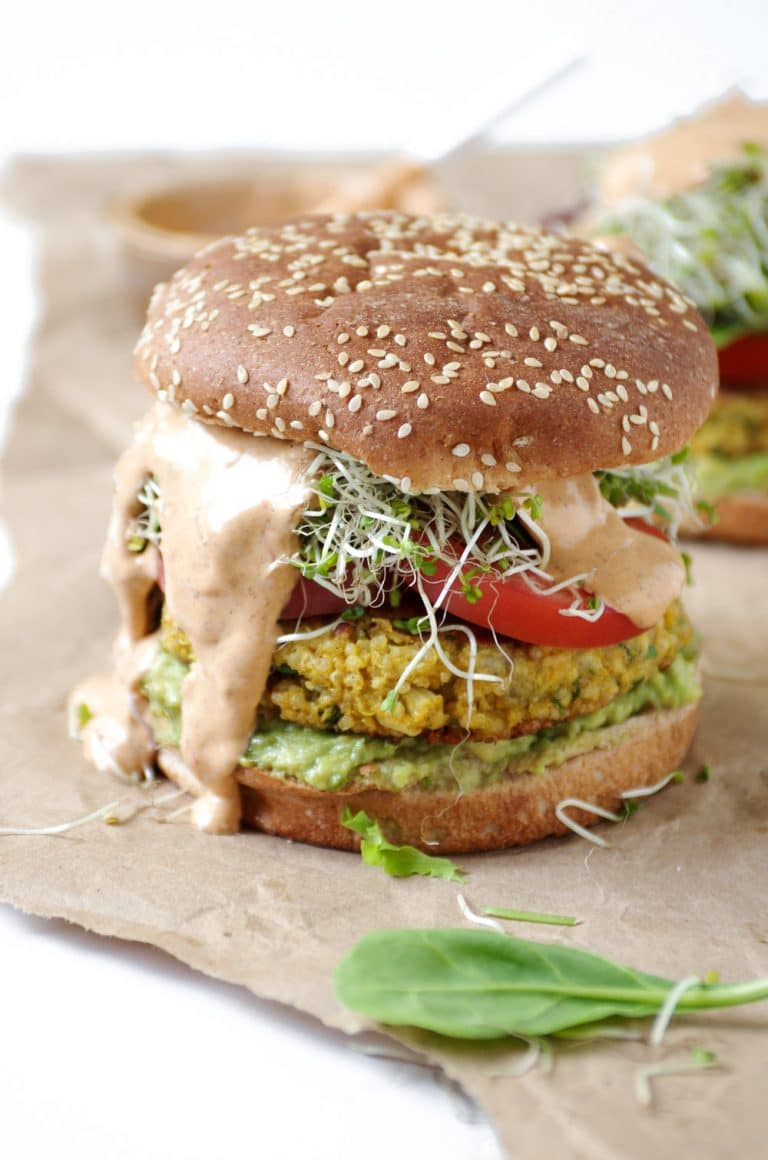 Easy Cauliflower Veggie Burgers with Avocado and Chipotle Mayo dripping out sides on brown paper