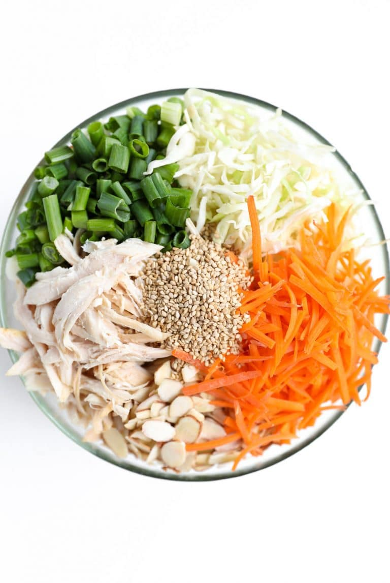 glass bowl of chicken, almonds seeds, onions, cabbage and carrots
