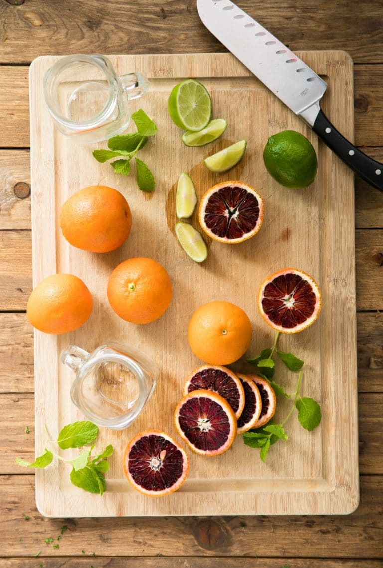 blood oranges, limes, mint on cutting board with knife and mason jars
