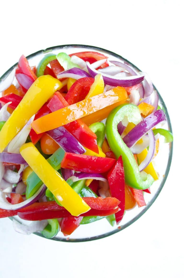 bowl of sliced red onions and multicolored bell peppers