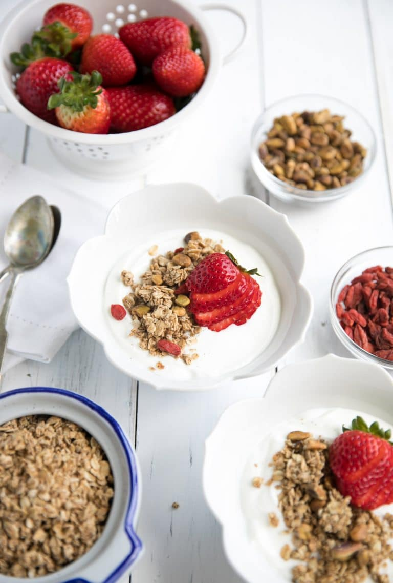 close up of homemade Oat Granola in two bowls with yogurt and strawberries