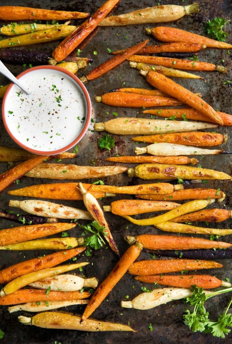 Roasted Carrots on a sheet pan with bowl of Lemon Tahini Sauce