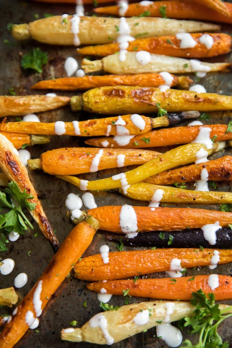 close up of Roasted Carrots on a sheet pan drizzled with Lemon Tahini Sauce