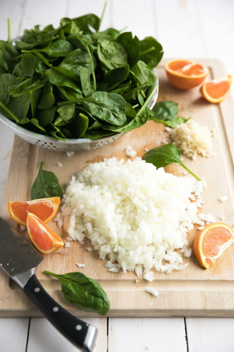 cutting board with chopping onions spinach and sliced oranges