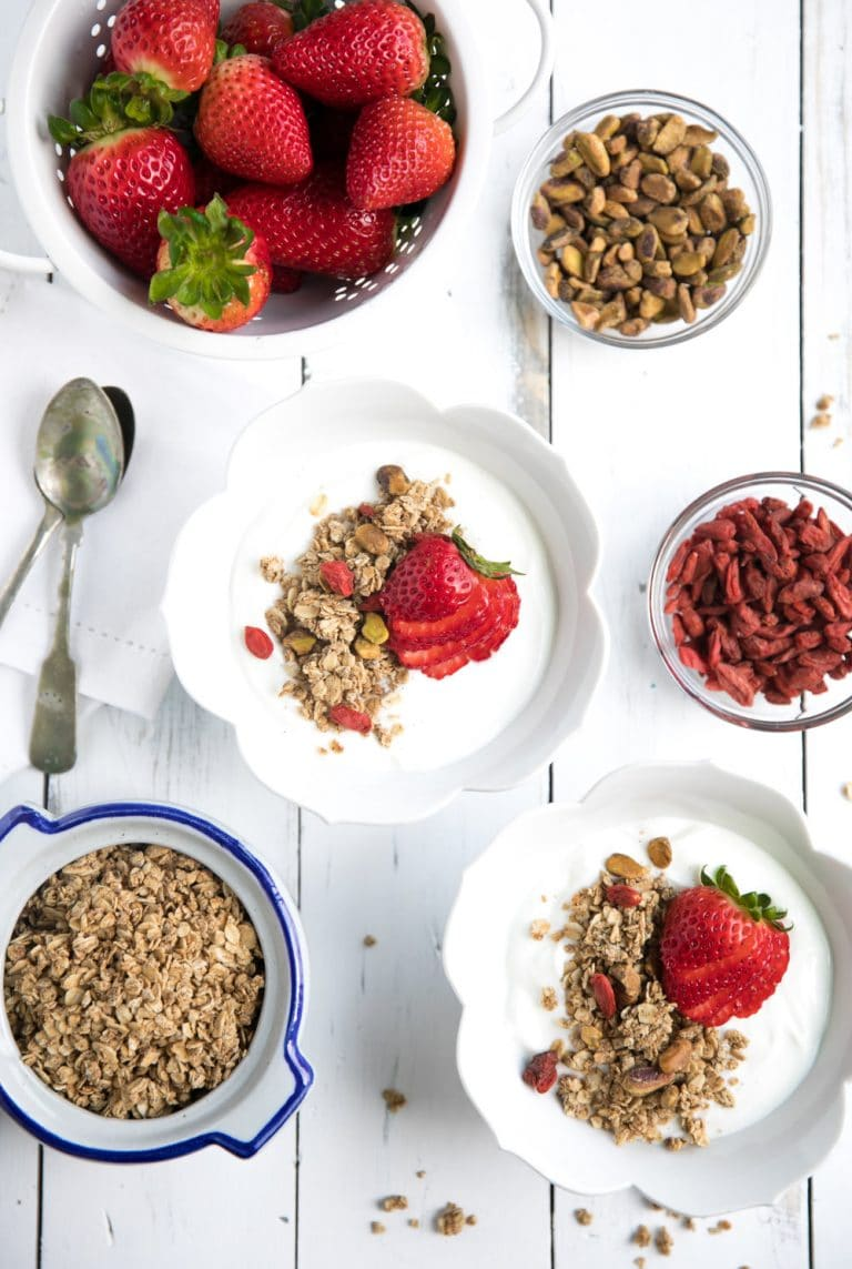 homemade Oat Granola in two bowls with yogurt and strawberries