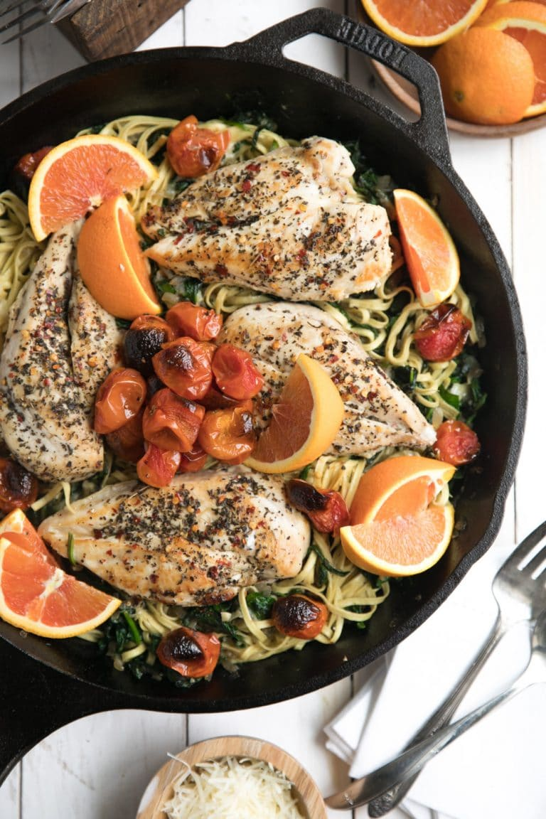 skillet full of Chicken and Spinach Linguine Skillet with Roasted Cherry Tomatoes with sliced oranges