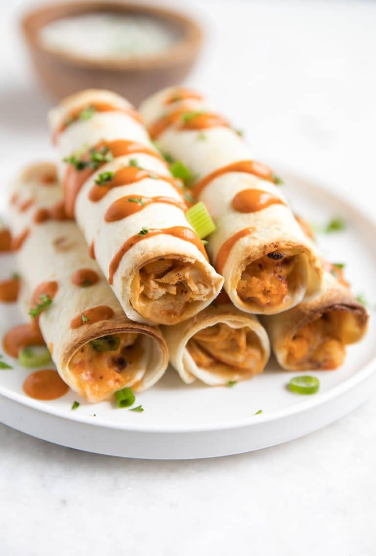 6 stacked Buffalo Chicken and Cauliflower Taquitos on plate